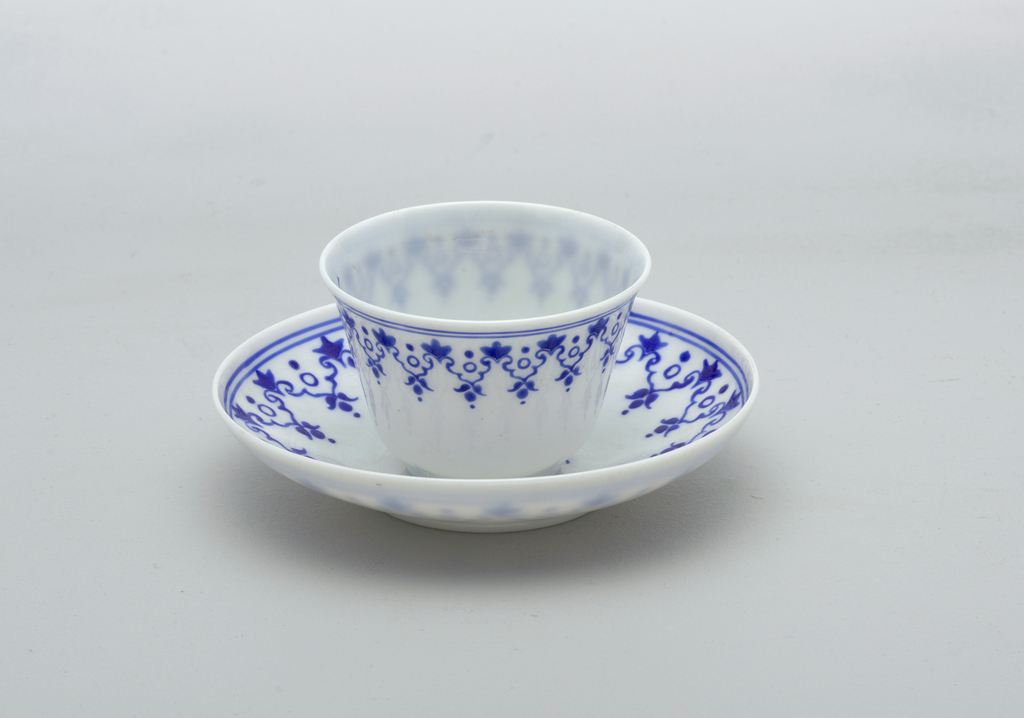 White glass with blue painted decoration.  House and tree central decoration on saucer.