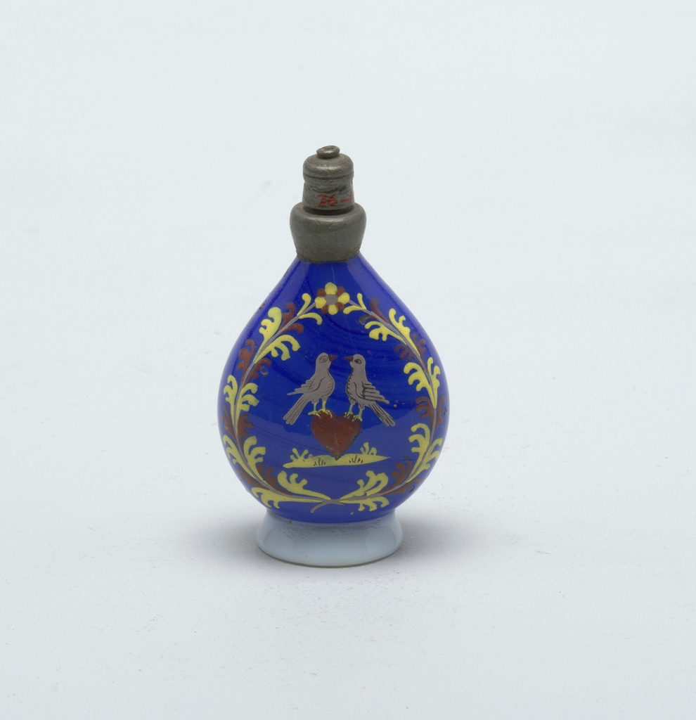 Cobalt blue bottle with silver twist-on stopper.  Painted love birds central figures