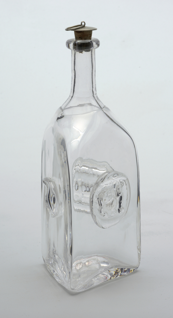 Clear glass triangular bottle with cork and silver stopper