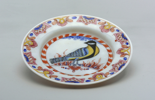 White glass plate with painted decoration.  Large bird central figure.