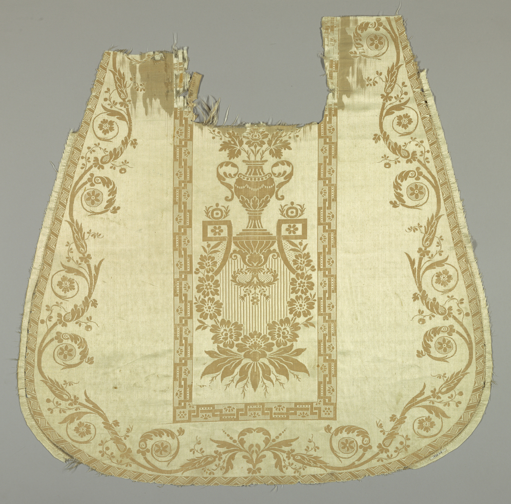Shaped panel, possibly woven to be the front or back of a chasuble, with a narrow geometric outline. In center, a design of an urn on a bracket over a floral garland.