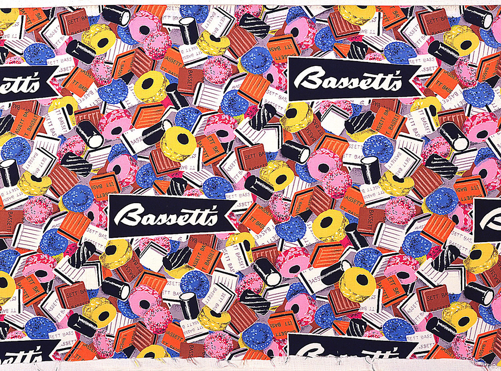 "Printed textile with an overall pattern of licorice candies in black, brown, blue, yellow, orange, pink and white, with banners reading ""Bassett's"" in white on black."