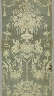 Long, pieced panel from the Directoire period with symmetrical design of bouquet of flowers, seated cupids, and a pendant frame surrounded by peacock feathers and enclosing addorsed birds on either side of palm tree. White raw silk in twill on pale turquoise satin ground horizontally ribbed from thick wefts. Pink and white striped satin selvages with four-cord edges.