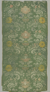 Green textile brocaded with pink and yellow silk showing symmetrical pattern with ribboned bouquets along central vertical axis, and serpentine florals on either side.