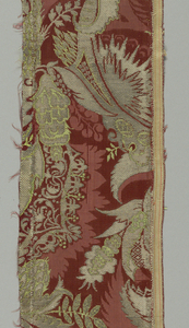 Fantastic leafy forms and entwining plants form a motif in metallic edge with light green plants one above the other and side by side for a continuous pattern. The background is dark red and damassé, the pattern of which forms a narrow shadow-edge to the motifs.