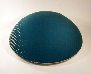 Hemispherical in form with blue upholstery, the lower half shows white dots that increase in size towards the bottom.