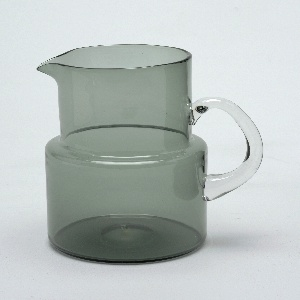 Stepped cylindrical form of transparent grey-green glass; applied D-shaped handle of clear glass.