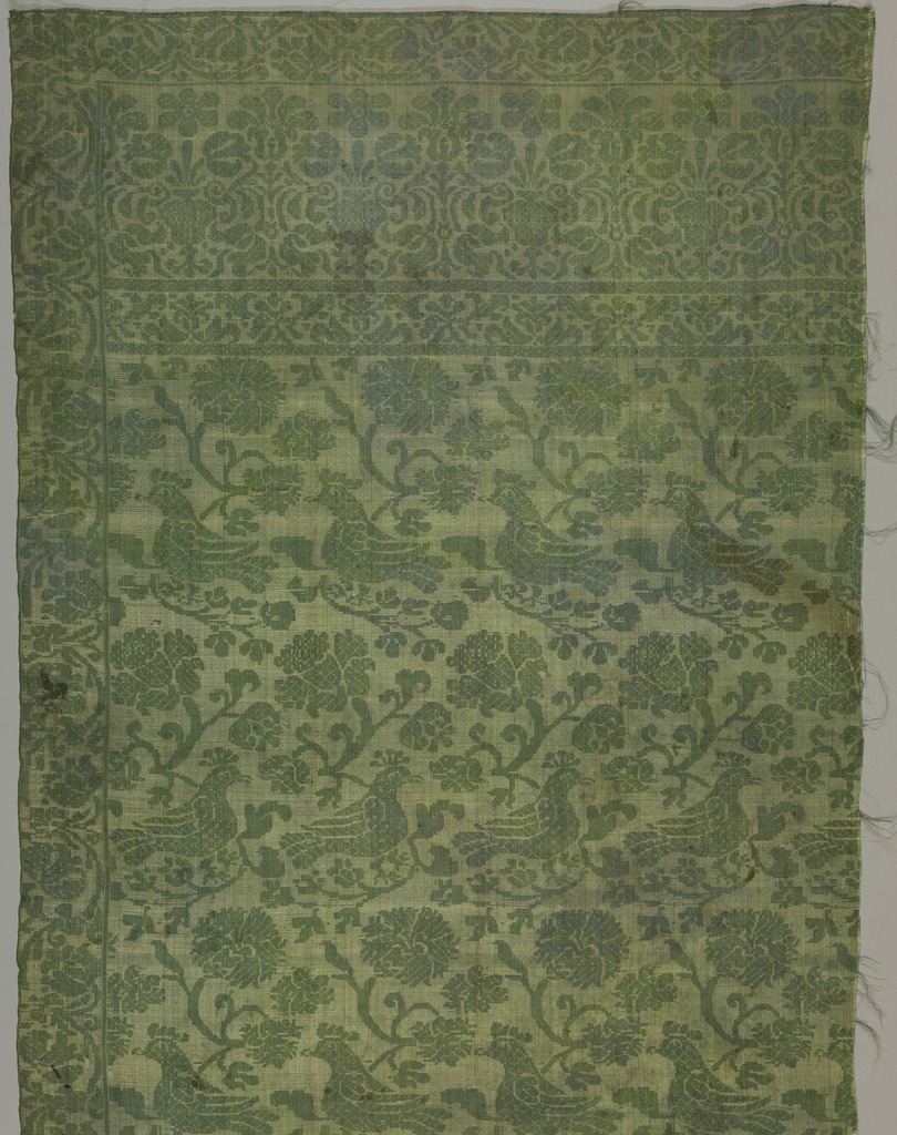 Reversible fabric in green and tan silk in a pattern of alternating horizontal rows turning left and right. One row has a double branch with one side turning up and ending in a decorative blossoms, the other side turning down and supporting a perched crested bird. Wide floral border rinceau border along right side and across top.