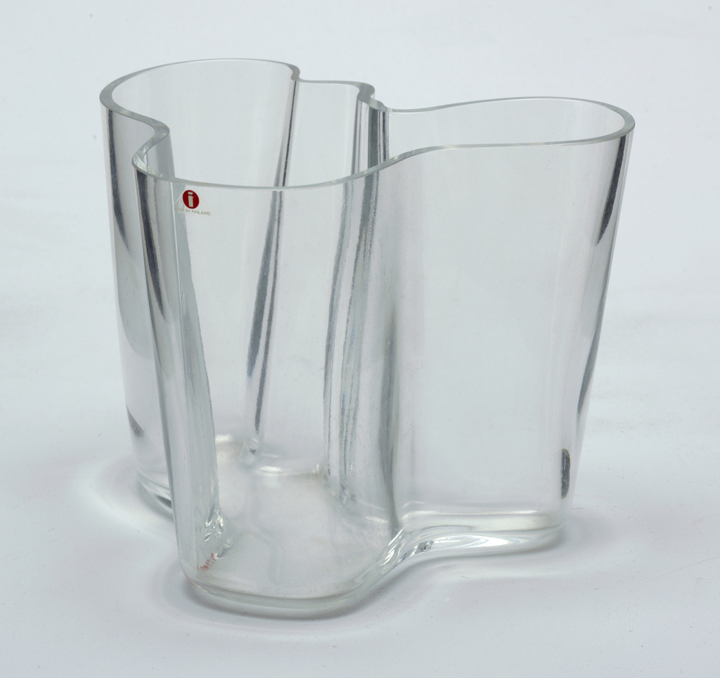 Tall, irregularly shaped clear glass vase with flat bottom; thickness of wall uniform throughout.