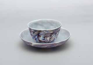 White glass with slight blue cast.  Blue/purple glass decoration in horizontal swirl pattern.