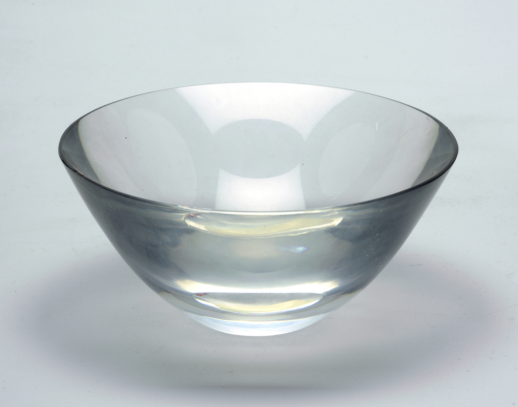Clear, slightly curved, thick-bottomed circular bowl flaring to thin rim.