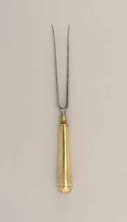 """Two long tines, pointing slightly outwards, rounded shoulders, baluster- shaped neck. Tapered cylindrical handle with round top, engraved floral pattern and rozette on the top. (Initial """"A""""?)"""
