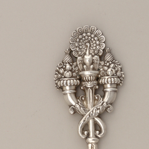 Tapering blade or pin with terminal in relief cast with entwined double cornucopia topped by a peacock.