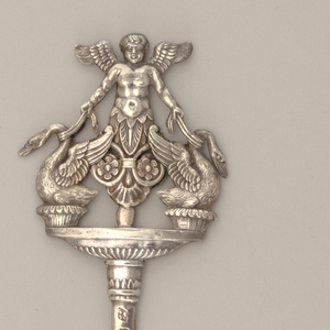 Flat tapering pin or skewer topped by relief cast of winged putto with a pair of swans.