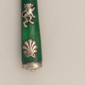 Three short tines, slightly curved shoulders, flat neck and rounded bolster. Ivory handle, painted green. Three silver appliques on each side of the handle in the shape of a lion and two scallops. Silver mount on the end of the handle has a floral decoration.
