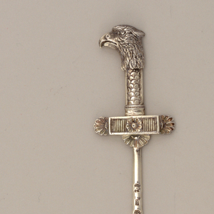 Tapering pointed pin or blade, cast relief terminal in the form of a palmette-embellished bar topped by an eagle's head.