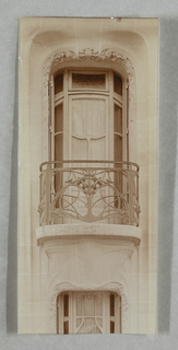 Photograph of a window on the facade of Hector Guimard's house on a higher story. Window has a metalwork balustrade.