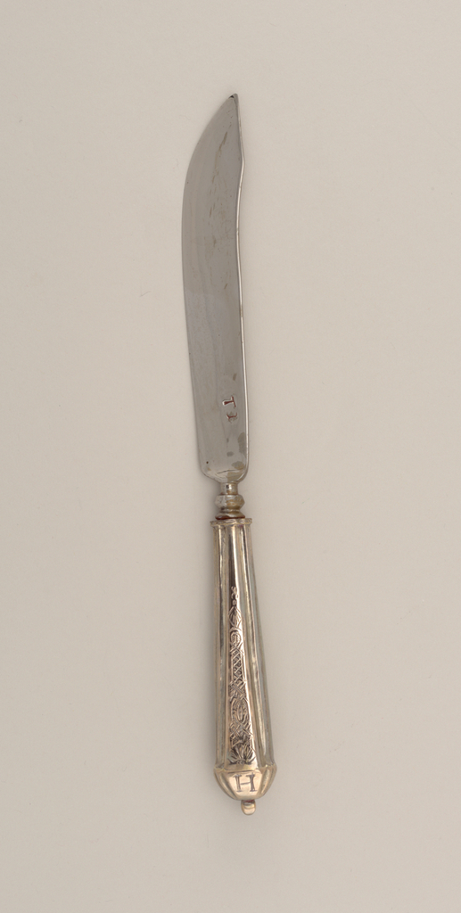 """Saber-shaped blade with concave bolster. Tapered silver handle with segmented panels to form rectangular profile. Front and back panels chased with decorative pattern fluted end with raised knop. Handle engraved at end with """"A"""" (converse) and """"H"""" (reverse)."""