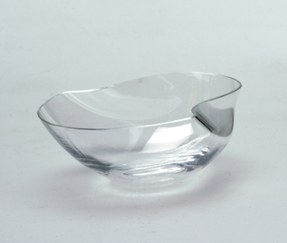 Thin-bodied transparent cup of irregularly curved and pinched form with thin rim.