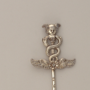 Tapering, pointed, flat pin or blade. Relief cast terminal with pair of outstretched wings, topped by a caduceus and head of Mercury.