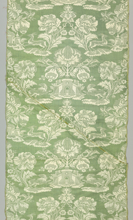 Green and white silk damask in a symmetrical pattern of flowers and a castle flanked by rampant lions and addorsed stags and birds.