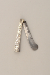 Sabre-shaped blade. Handle straight-sided, flaring towards the end. Engraved floral decoration with a lion in the cartouche on front and back. Diamond-shaped pattern along the sides. Blade folds into handle.