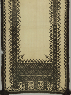 Oblong panel of heavy cream white hand-woven linen embroidered in black wool and trimmed with fringe of black wool and black tassels at each corner. Borders at side and deep border at end, with a highly stylized plant form, detached and placed at a slant, above borders of geometric forms. Cross and satin stitch.