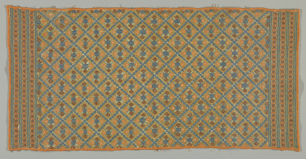 Panel embroidered in blue, orange and rust-colored thread in an allover diamond pattern. Accented with metallic thread.