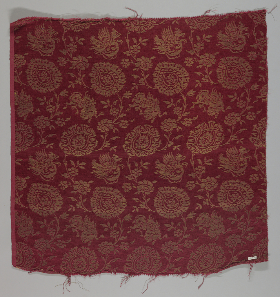 Reproduction textile adopted from a Lucchese design in the collection of the Cooper Union Museum. Dark red with metallic gold threads in a pattern of serpentine branches with ogive blossoms and Chinese-inspired monsters and senmurvs between serpentines.
