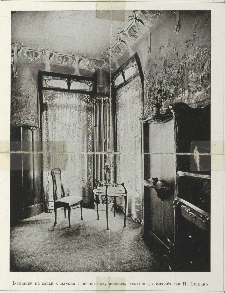 A photograph of a dining room designed by Guimard. There are two chairs in front of two large windows, as well as a side board for serving food.