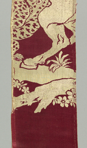 Rose satin ground with off-white weft patterning. Fragments show alternating vertical large-scale repeat vignettes of a horseman under attack by a leopard, a horseman with a raised scimitar fends off an attack by a lion, and a man standing before a large palm tree stabs a leopard. Men are dressed in a variety of Eastern costume.
