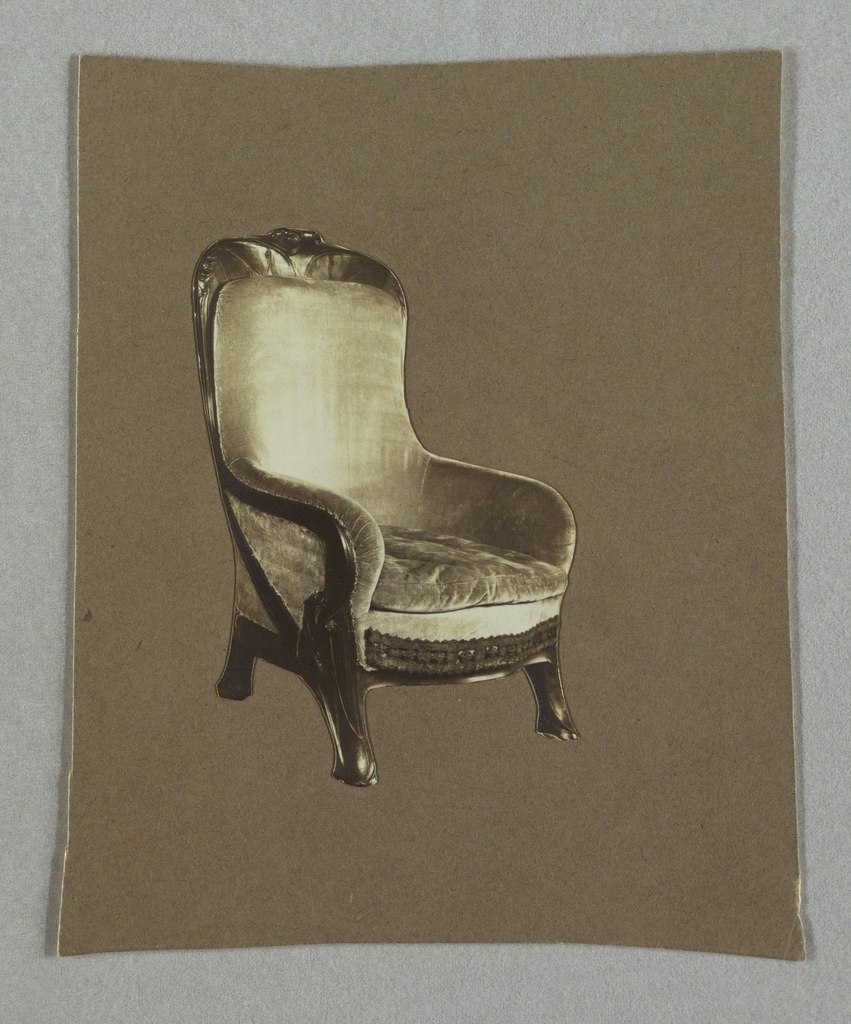 A photograph of a chair designed by Hector Guimard that is upholstered in fabric and has a carved wood top and legs.
