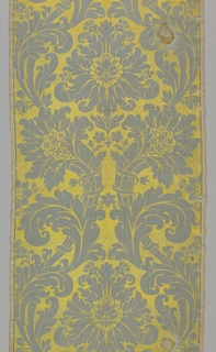 Light blue satin design on ground  formed by extra yellow silk weft floated out on surface of fabric and tied down in twill by blue silk warp. White linen functional weft hidden. Very large-scale symmetrical design of central pomegranate blossom flanked by great swinging acanthus branches terminating in massive ornamental flower. Both selvages present.