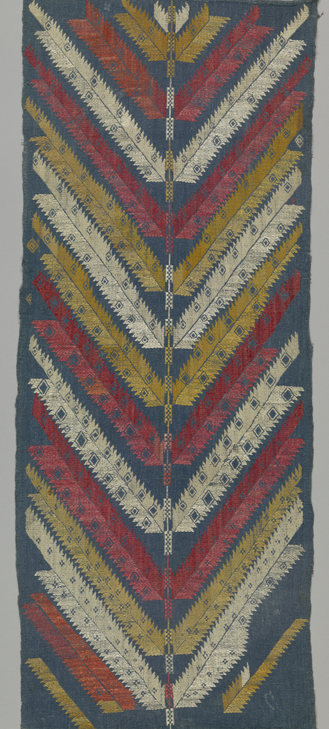 A very stylized tree form, with sawtooth-edged braches springing diagonally in from a central trunk to form a chevron. The branches are decorated with voided squares and tiny crosses. Embroidered in red, tan, and white silks on a blue linen ground.