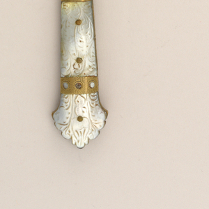 Sabre-shaped blade with a profiled upper edge, rounded bolster. Flaring rectangular handle, carved mother-of-pearl. Brass rivets on both sides of handle. Brass mounts and band along the side of handle decorated with engraved geometrical and fish-shaped forms.