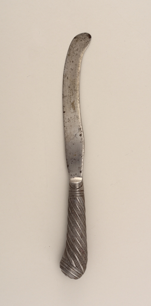 Integral. Saber-shaped blade, curved end. Pistol-butt handle with overall spiral pattern. End decorated with molded concentric rings and central button.