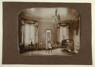 Photograph of Madame Guimard's bedroom at Hector Guimard's house at 122 rue Mozart. Photograph depicts two windows, a chair and mirror in the center, and a vanity on the right.