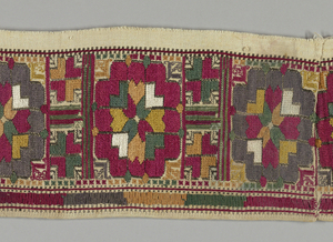 Two borders, probably from sleeve or bottom of dress, worked in silks in red, yellow, orange, white, and outlines of black. Design shows a stylized flower head, with heart-shaped leaves at the center and small leaf-shaped corner designs. Repeat about 3 inches wide, separated by a narrow border of completely stylized smaller flower-head. A bottom border of drawn work, made by whipping groups of threads in similar colors to embroidery, about 1/2 inch wide.
