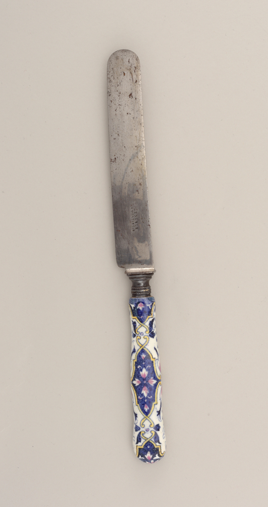 Straight steel blade with earthenware handle of yellow arabesque framed reserves enclosing pink flowers on a blue ground, all on white ground.