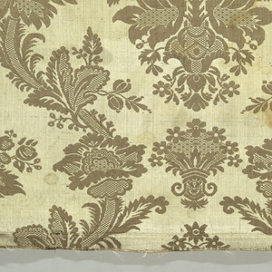 Tobacco-brown silk with a large scale repeat of vase and flowers in continuous ogival framework of leaves and flowers with checkered and diapered details.