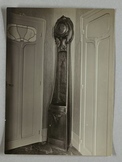 Photograph of a clock designed by Hector Guimard within his house. His signature abstracted floral motif style is present within the design of the clock.