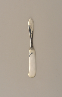 Flat silver blade and handle formed as one piece. Handle with rounded, pointed terminal.