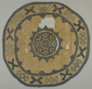 Large rounded applique in cream and two shades of blue. Border design includes stylized forms and small discs, one of which retains red color. Center medallion is blue with pattern suggesting leaves or wings reserved in cream ground; plus remains of inserts of white, blue and red silk are visible.