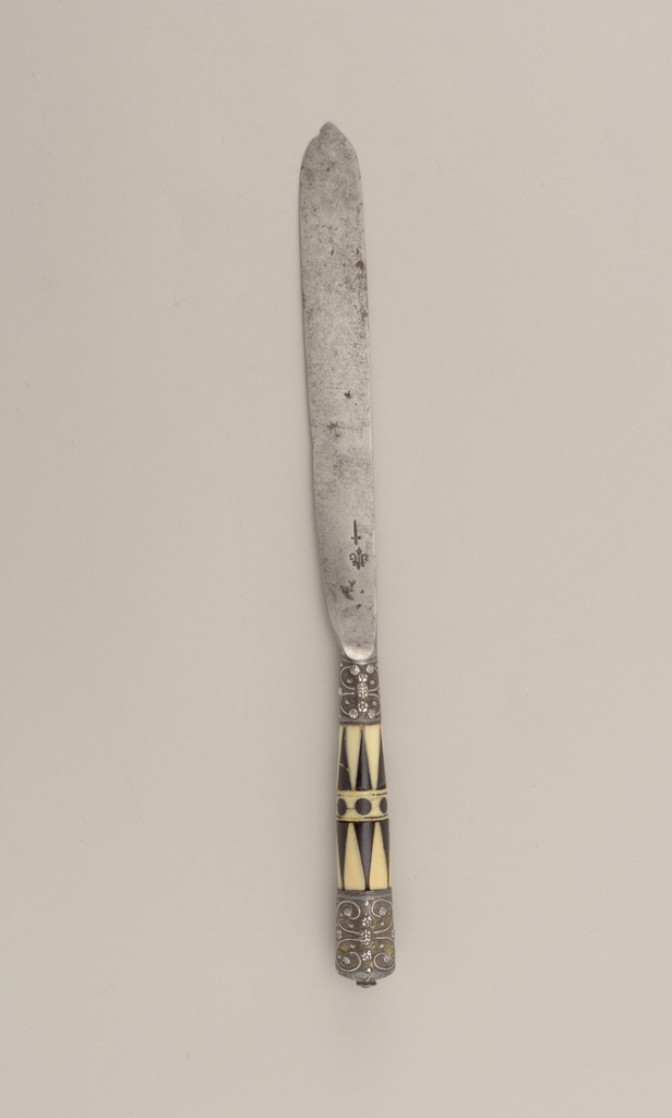 Blade with straight sides and leaf-shaped point. Hollow bolster, ferrules silver gilt with floral pattern. Tapered handles are ivory and bone in triangular pattern. In the middle of the handle black inlaid dots and two horizontal bands. Silver-gilt caps with floral pattern on the end of the handle.