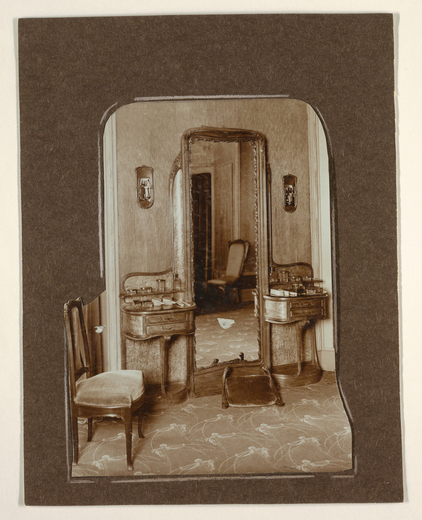 A photograph of the interior of Hector Guimard's house with furniture designed by him. Pictured are a mirror with two side tables and a chair.