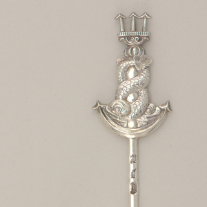 Flat, tapering pin or blade with relief cast terminal with two dolphins entwined around a trident.