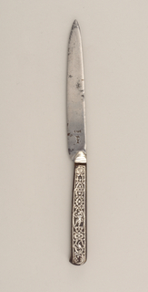 Blade has straight upper edge, tapering towards the point. Drop bolster, handle flaring towards the end, decorated on front and back with tortoise- shell, inlaid with silver decorative pattern: scrolls, scallops, acanthus leaves, a squirrel and a man in costume in one side; a bird and a nude figure on the reverse.