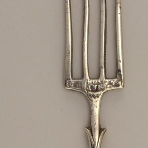 Small fork has four flat tines, square shoulders. Foliate handle with three ribs in center, volute scroll end.