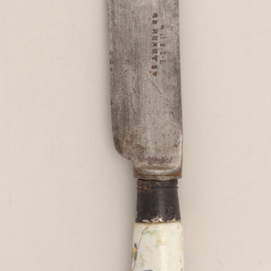 Straight sided blade with rounded ends. Plain silver ferrule. Pistol-shapedhandle, earthenware, white ground with floral sprays in blue, yellow, greenand purple. Small metal cap at the end of the handle.