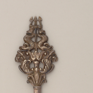 Tapering pointing blade or pin; cast terminal embossed with cat-tail topped acanthus fronds below a pair of opposing dolphins centering a trident.